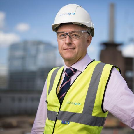 National Grid Head of Real Estate Phil Edwards portrait with out of focus Battersea site in the background