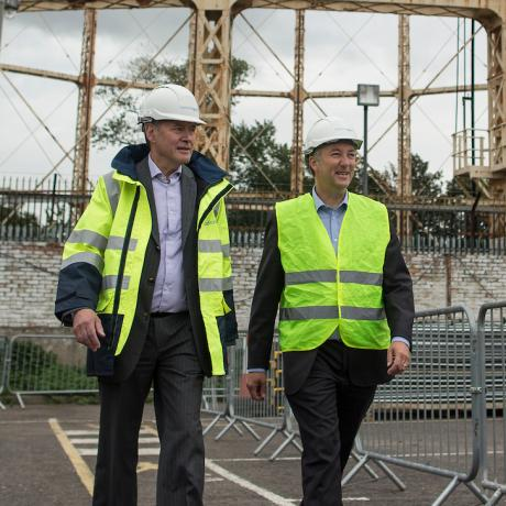 Two National Grid representatives walking away from a gas works structure