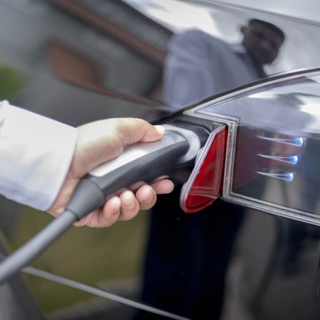 An image of a man plugging a charging point into a black electric vehicle