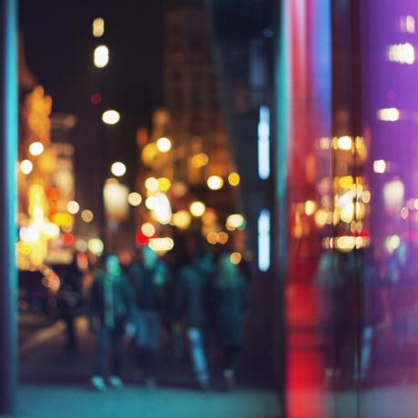 An out of focus city view with well-lit buildings and people walking along the pavement