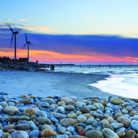 A beach landscape at sunset with wind turbines
