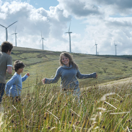 Woman and two children running through grass in front of hill with wind turbines - used for the homepage for the National Grid story '8 ways National Grid is tackling climate change in the UK'