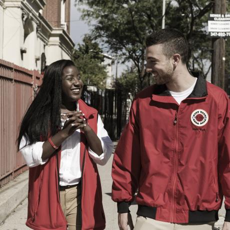 Two young people smiling and walking down an American sidewalk