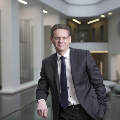 National Grid Chief Executive John Pettigrew standing in front of white office interior