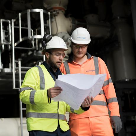 Two National Grid workers looking at a sheet of paper with an industrial framework in the background - About us