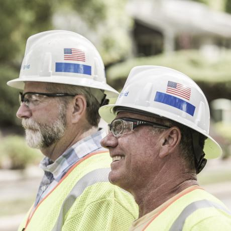 A close up image of two National Grid workers in front of trees and a house - Putting customers first in Rhode Island