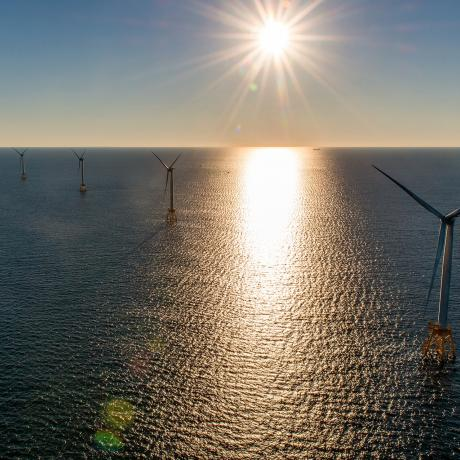 The sun shining over the ocean and a group of wind turbines - offshore first for the usa
