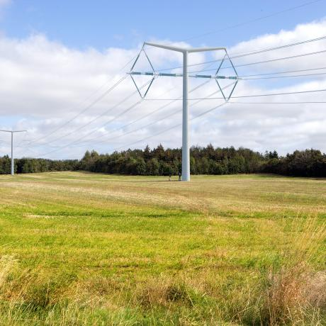 A green stretch of field under a blue sky with electricity pylons standing tall - Innovation