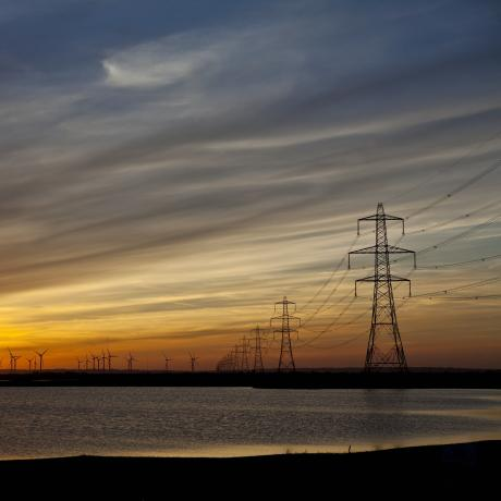 A beach at sunset with the sea coming in and electricity pylons dotted into the distance