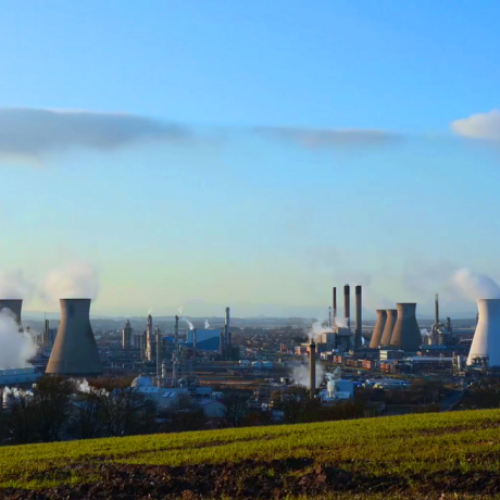 An image of a gas-fired power generation station with a blue sky and green grassy hill