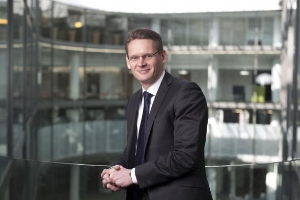 National Grid Chief Executive John Pettigrew standing in front of an out of focus office space