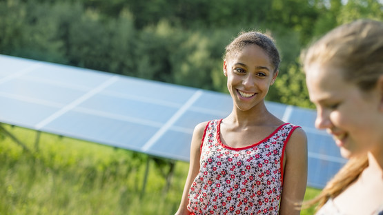 Young women with solar panel in the background
